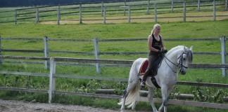 Eine Reiterin in einer Reitbahn.