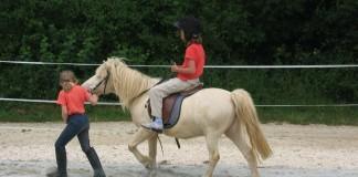 Kind wird auf Pony geführt